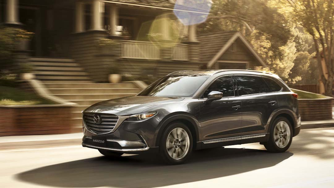 Image of a silver 2019 Mazda CX-9 driving on a suburban street.